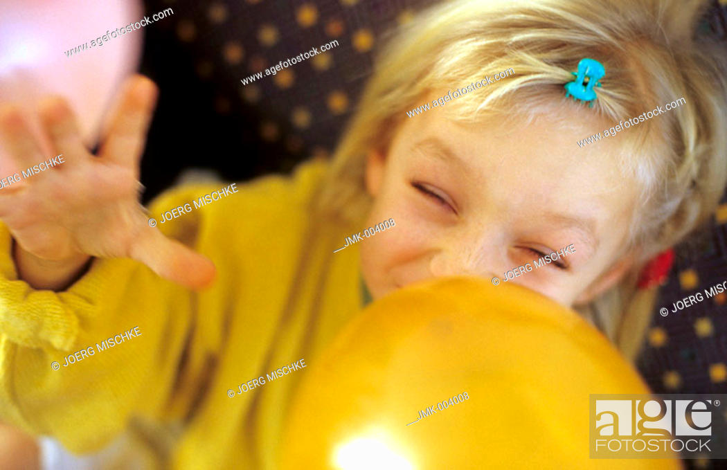 Stock Photo: A little girl, 5-10 years old, inflating a balloon.