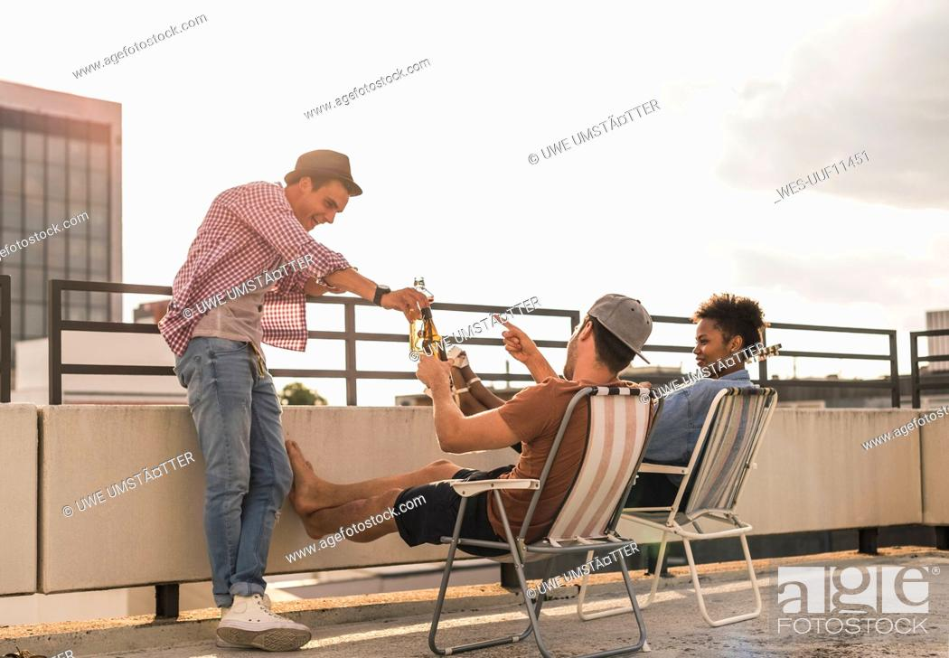 Stock Photo: Three friends having a rooftop party.