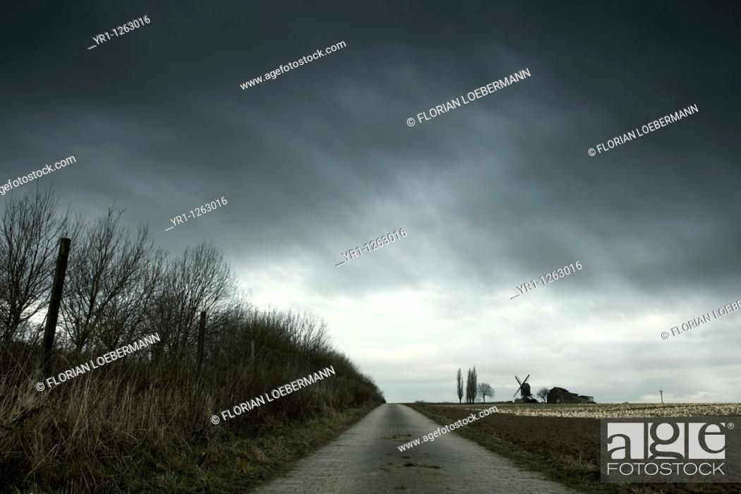 Stock Photo: Landscape with an old windmill during winter. Dramatic sky. Shot in North Rhine-Westphalia, Germany.