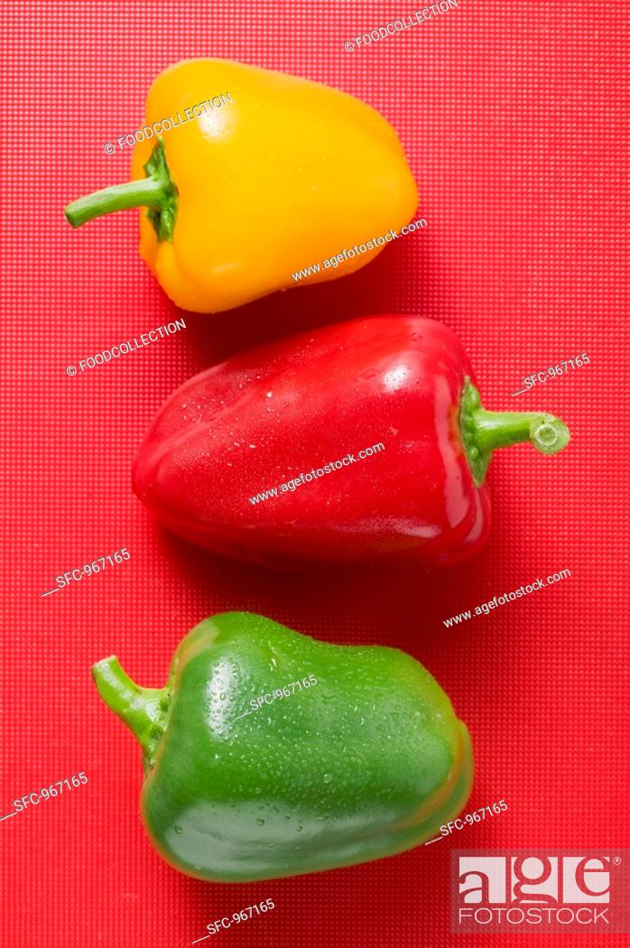 Stock Photo: Different coloured peppers with drops of water on red background.