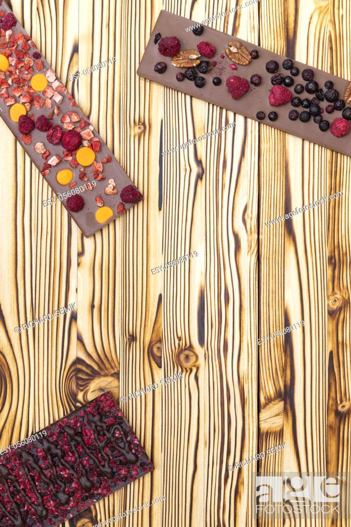 Stock Photo: different kinds of chocolate with dried fruits on a wooden board.