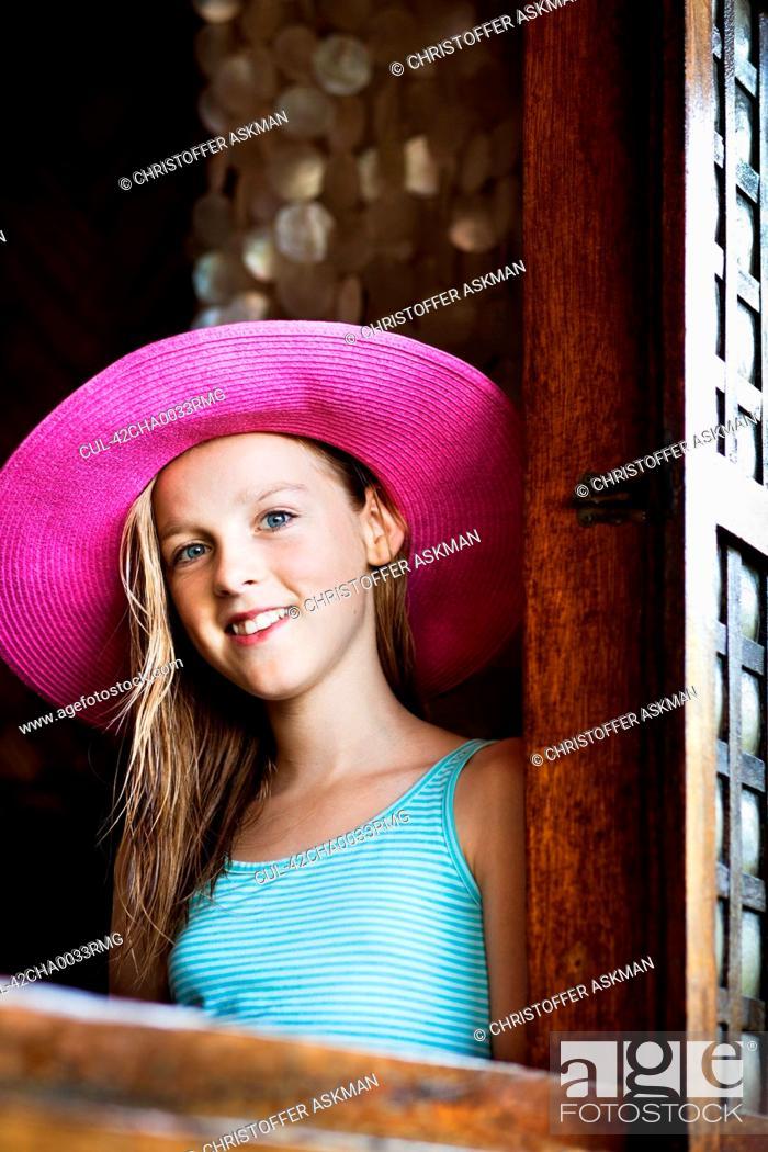 Stock Photo: Girl wearing straw hat at window.