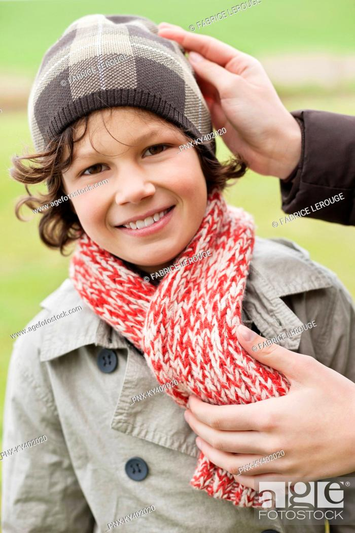 Stock Photo: Woman putting on warm clothing on her son.