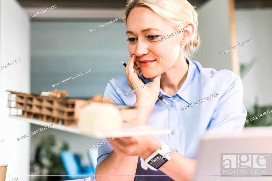 Stock Photo: Woman in office holding architectural model.