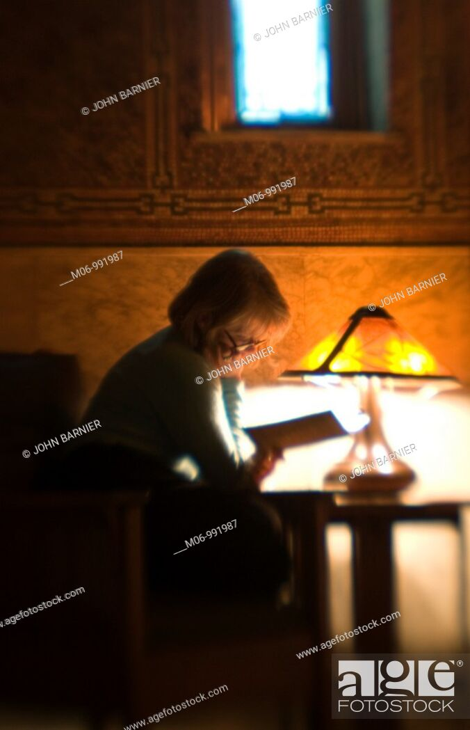 Stock Photo: Woman reading in a darkened room, sitting by a lone lamp.