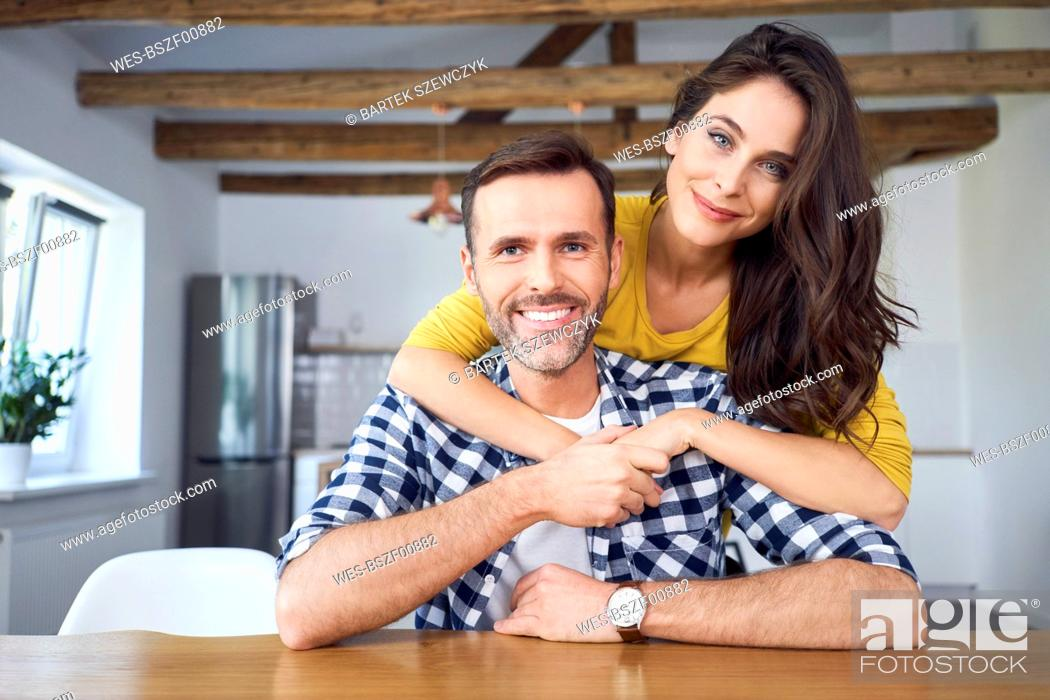 Stock Photo: Couple embracing, sitting at dining table.