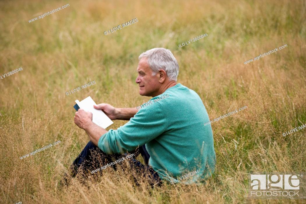 Stock Photo: A senior man sitting on the grass, reading a book.