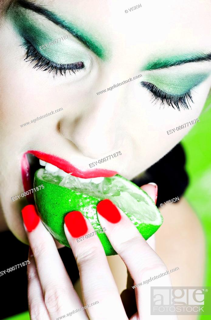 Stock Photo: beautiful woman portrait with colorful make-up and background biting citrus fruit.