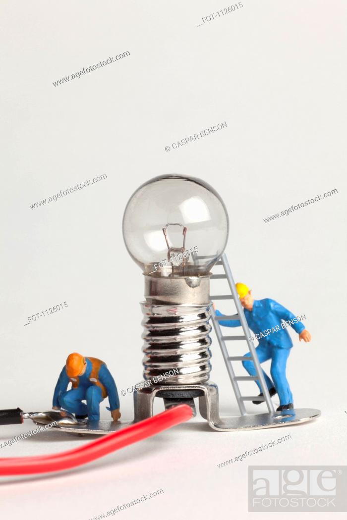 Stock Photo: Miniature electrician figurines working on a light bulb.