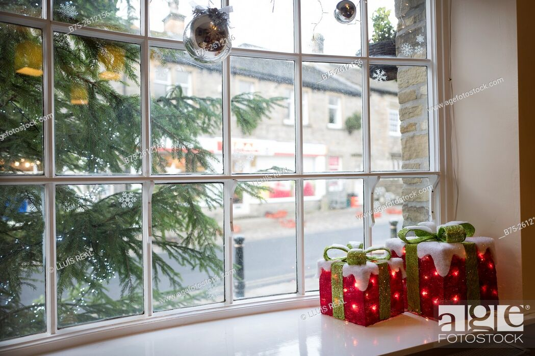 Stock Photo: Window of a house with Christmas decorations. Christmas tree and gifts. Grassington, North Yorkshire, Yorkshire Dales, England, UK, Europe.
