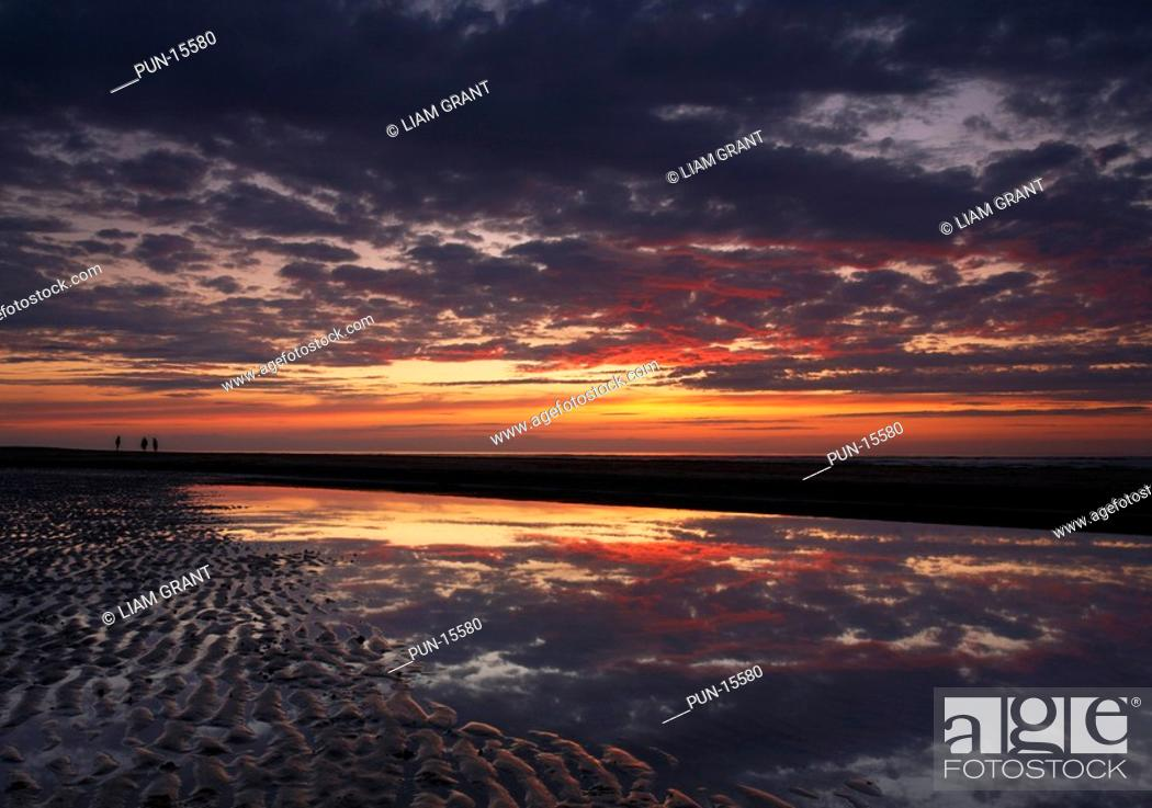 Stock Photo: Silhouettes of three people walking along the beach at sunset, Wells-next-the-sea, North Norfolk Coast, United Kingdom in summer.
