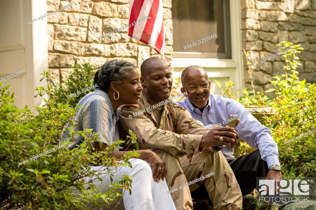 Soldier sitting on front stoop with parents and texting on
