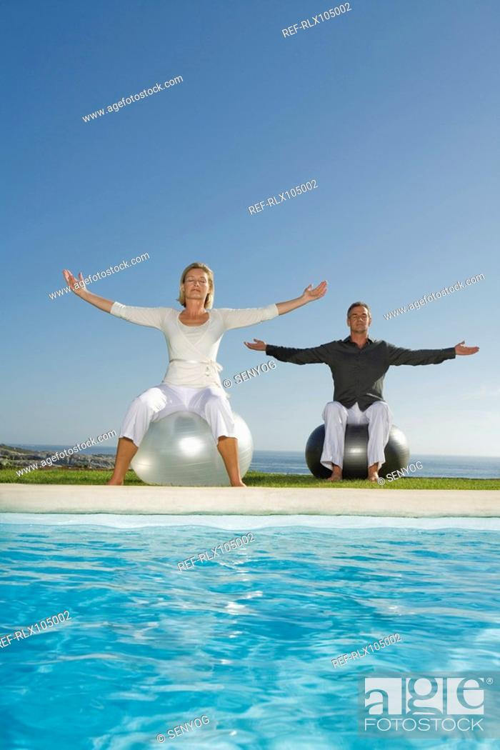 Stock Photo: Mature couple sitting at poolside on Gymnastic balls doing Pilates exercises.