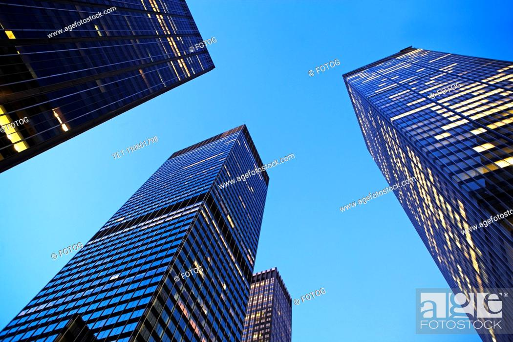 Stock Photo: USA, New York State, New York City, Manhattan, low angle view of office buildings illuminated at dusk.