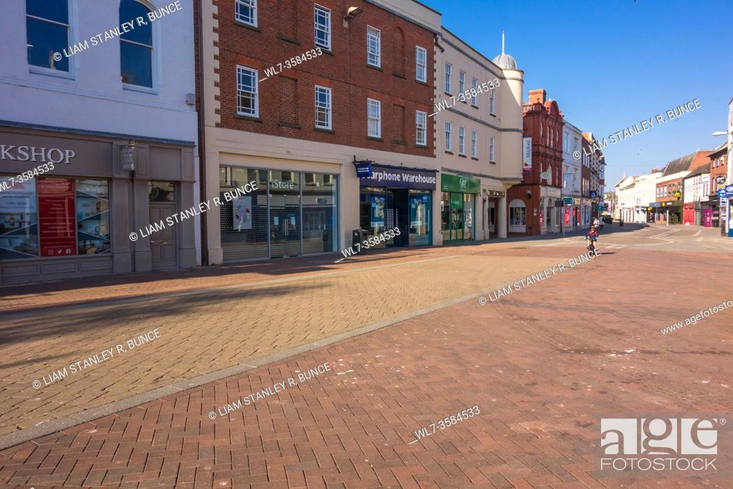 Stock Photo: A child cycling along a deserted Street during the Covid-19 lockdown Hereford Herefordshire UK. April 2020.
