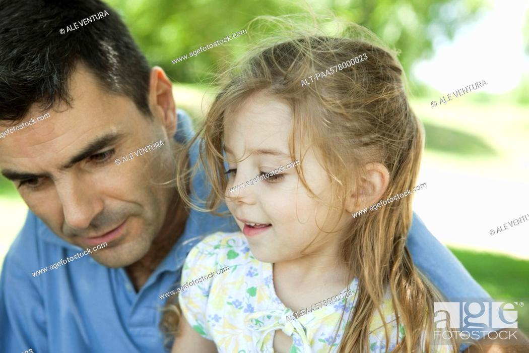 Stock Photo: Father and young daughter talking outdoors.