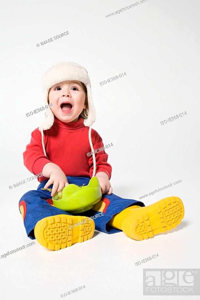 Stock Photo: A boy holding a bowl of grapes.