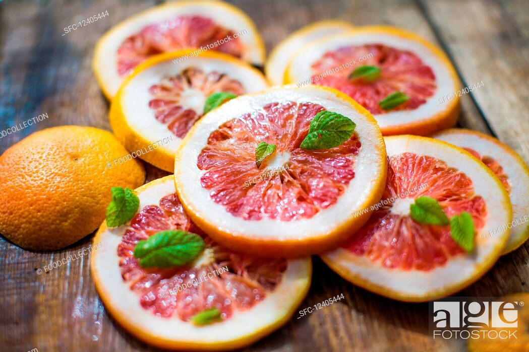 Stock Photo: Pink grapefruit slices with mint leaves on a wooden background.