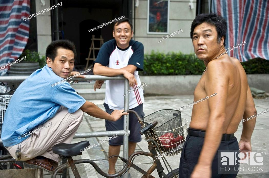 Stock Photo: three men in the street looking at camera. Shanghai, China.