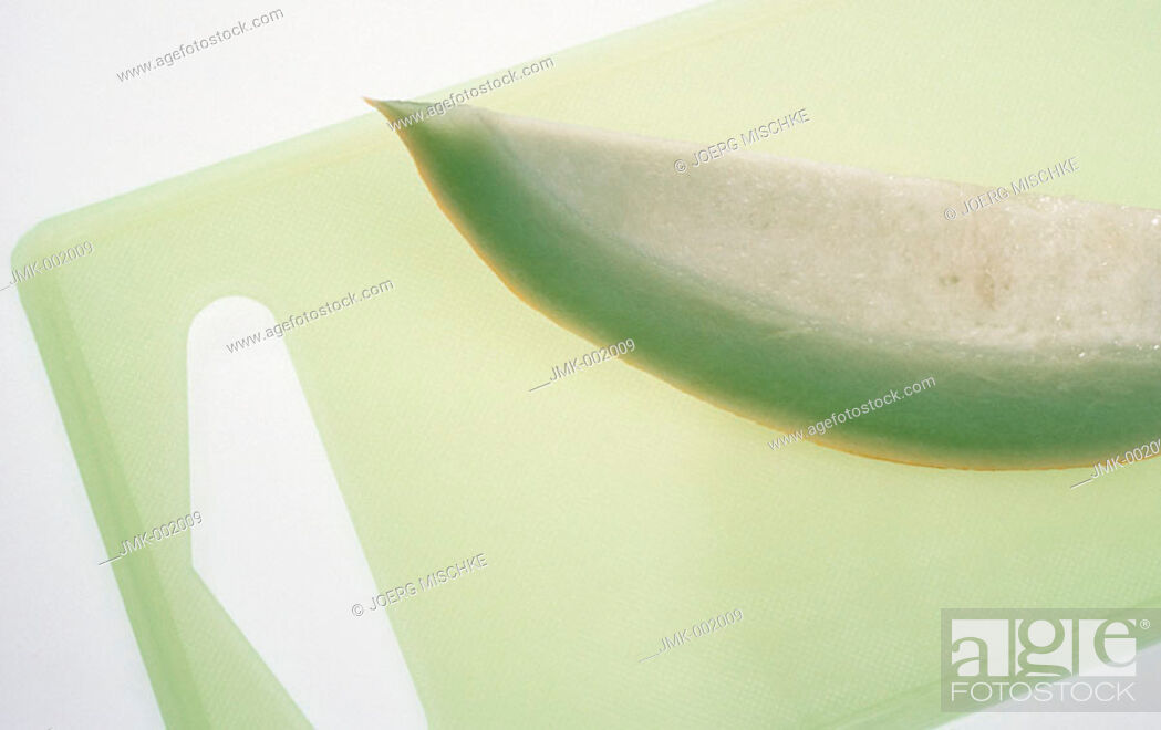 Stock Photo: A slice of melon on a chopping board, carving board.