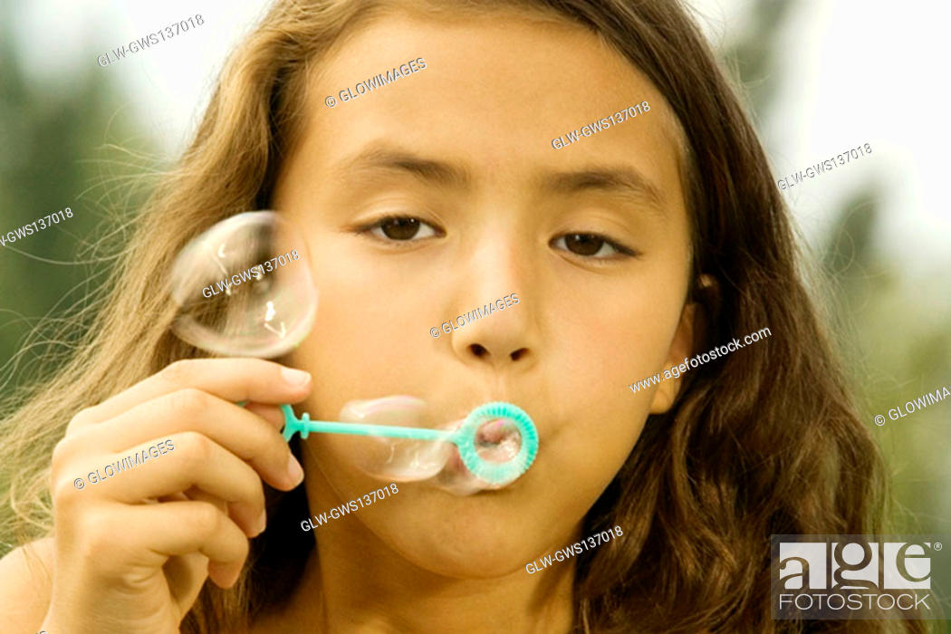 Stock Photo: Close-up of a girl blowing bubbles with a bubble wand.