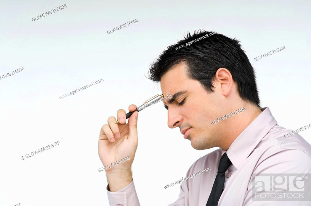 Stock Photo: Close-up of a businessman holding a pen and thinking.