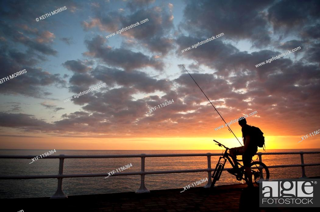 Stock Photo: The silhouette of a young man on a bicycle at sunset, about to go fishing, cardigan bay west wales UK.