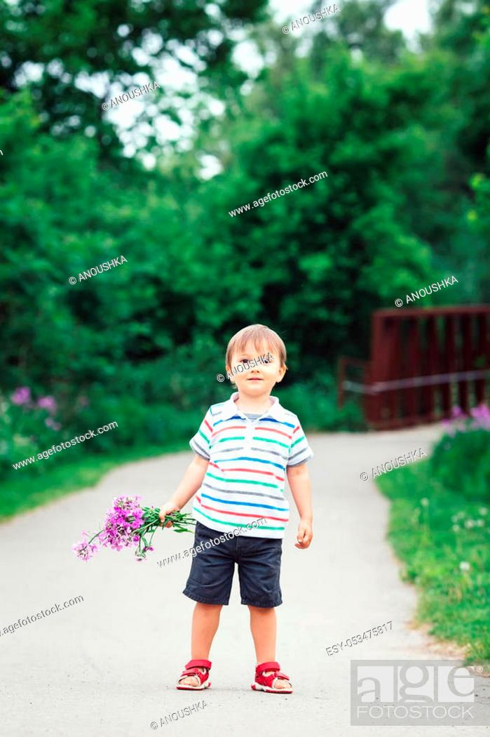 Stock Photo: Portrait of a cute adorable funny little smiling boy toddler walking in park with lilac purple pink flowers in hands on bright summer day.