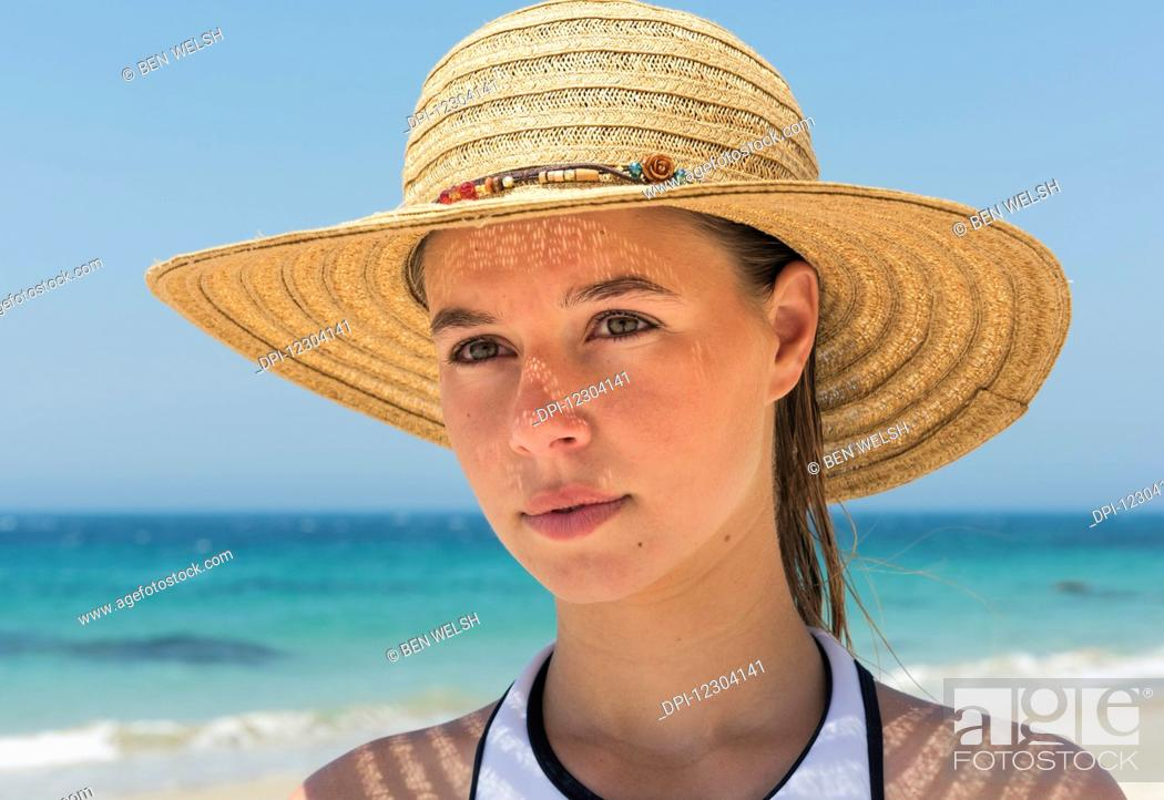 Stock Photo: Portrait of a young woman on the beach wearing a sunhat; Tarifa, Cadiz, Andalusia, Spain.