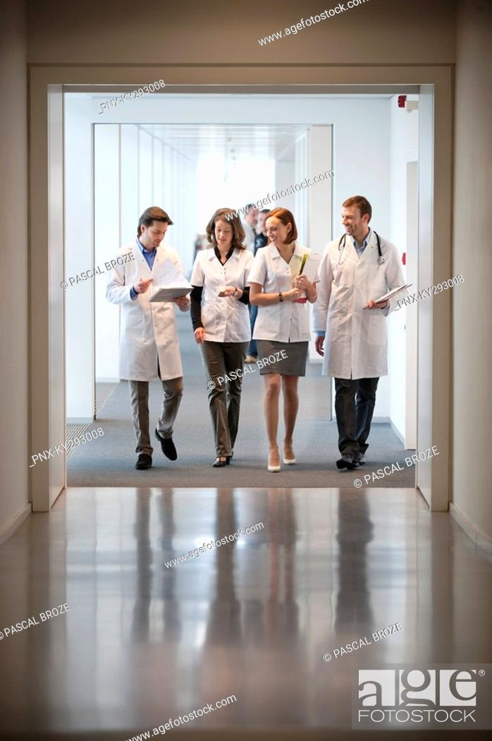 Stock Photo: Four doctors walking at the corridor of a hospital.