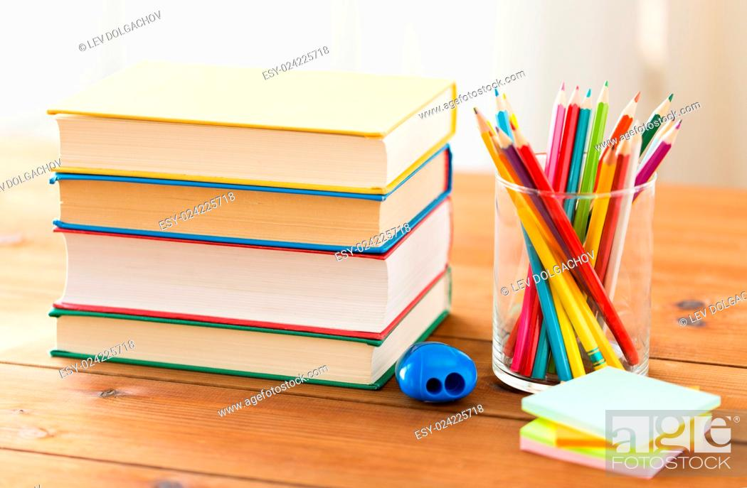 Stock Photo: education, school, creativity and object concept - close up of crayons or color pencils with books, stickers and sharpener on wooden table.