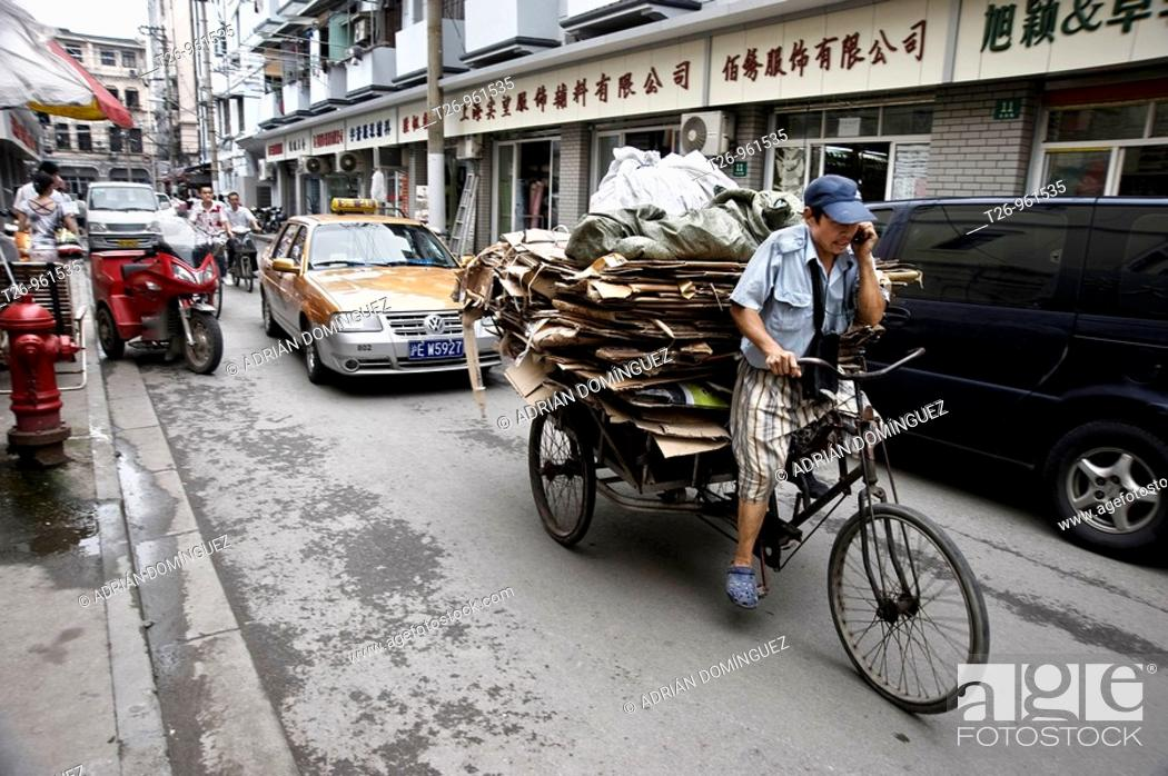 Stock Photo: a man on a bicycle carrying cartons. Shanghai, China.