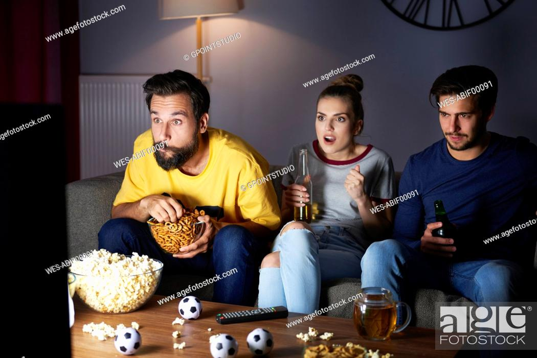Stock Photo: Excited friends sitting on the sofa watching Tv.