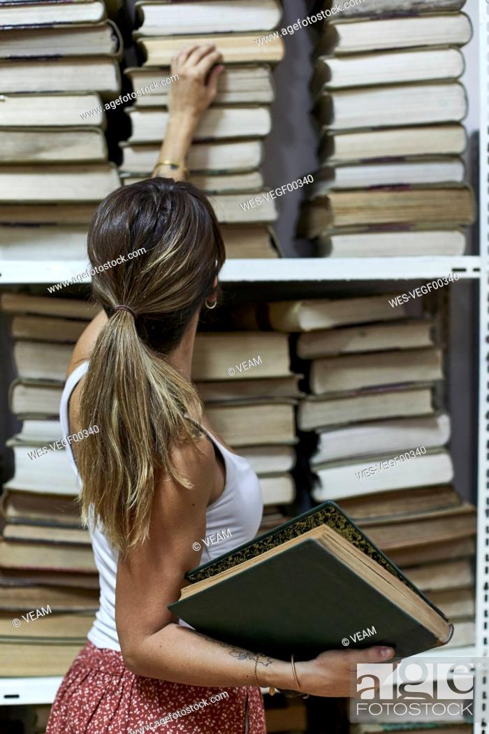 Stock Photo: Back view of woman checking the books at National library, Maputo, Mocambique.