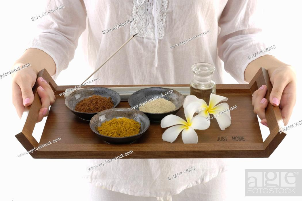 Stock Photo: Woman holding spa products in a tray.