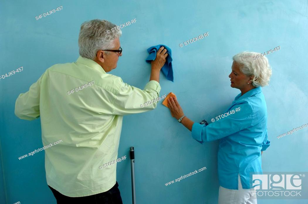 Stock Photo: Senior man and woman both cleaning the wall with cloth.