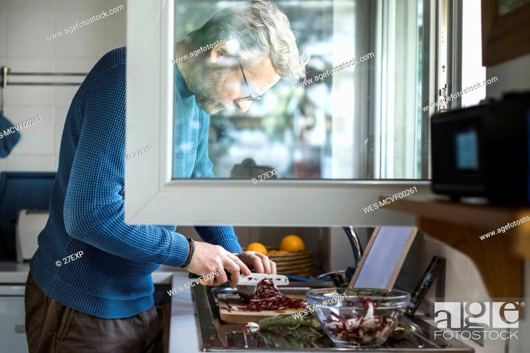 Stock Photo: Mature man preparing salad at open window in his kitchen.