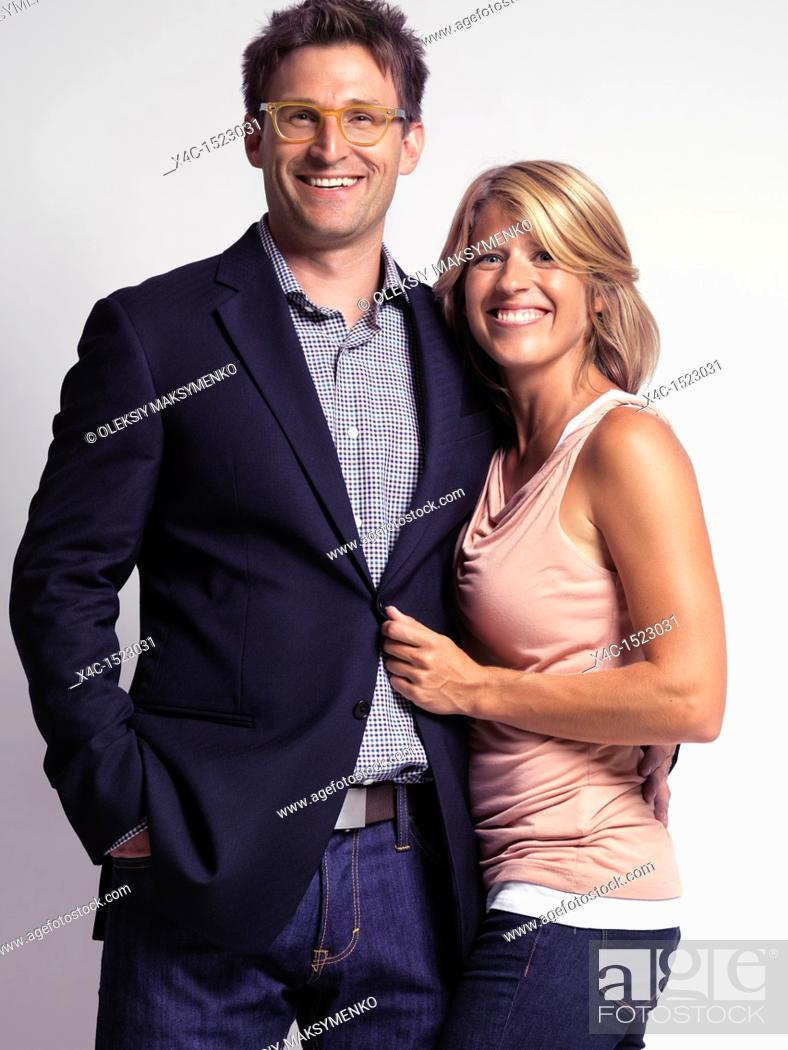 Stock Photo: Smiling casually dressed happy young woman and a man isolated on gray background.