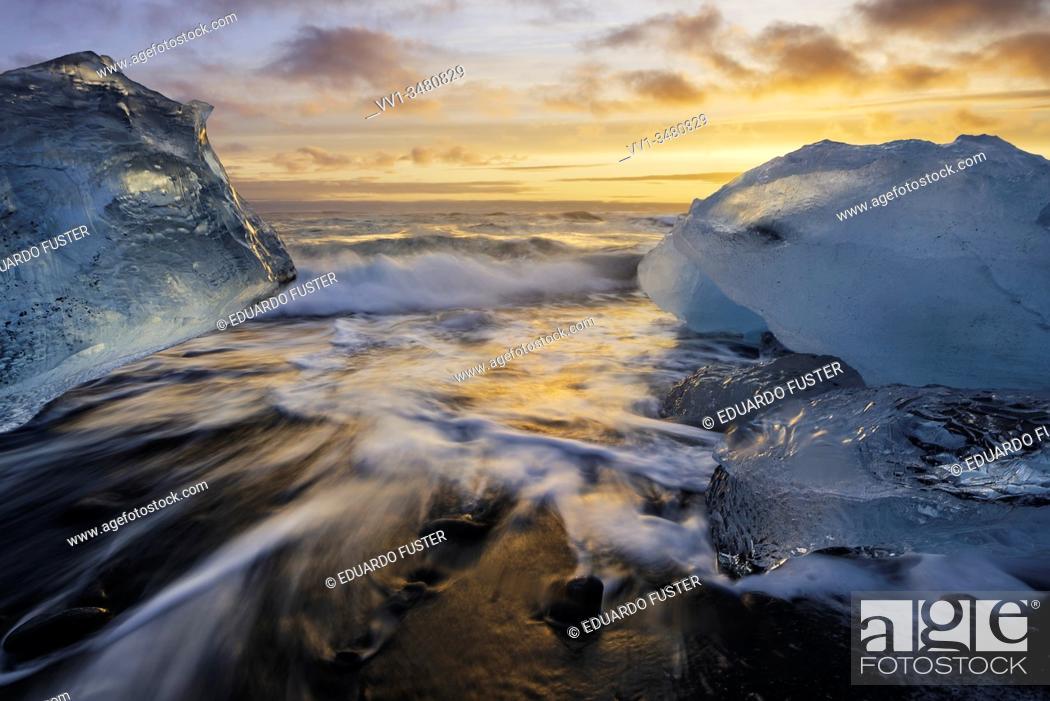 Stock Photo: Broken ice from washed up Icebergs on Jokulsarlon black beach at sunset Jokulsarlon South east Iceland.