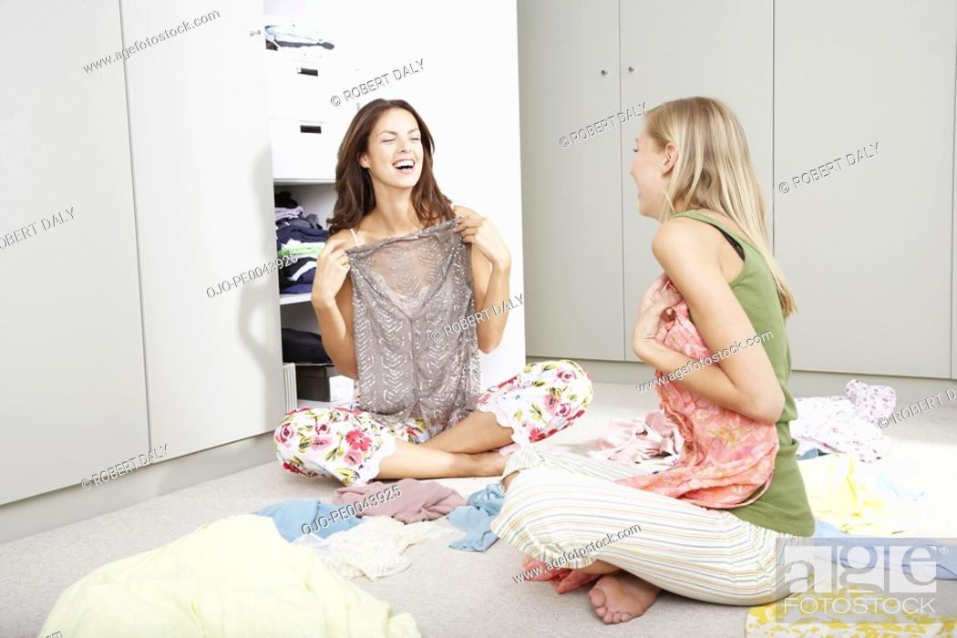 Stock Photo: Two girlfriends in a bedroom going through a closet.