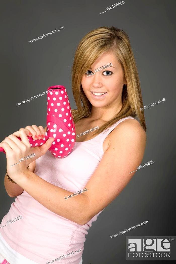 Stock Photo: Teenage girl posing on gray background with some attitude and a blowdryer.