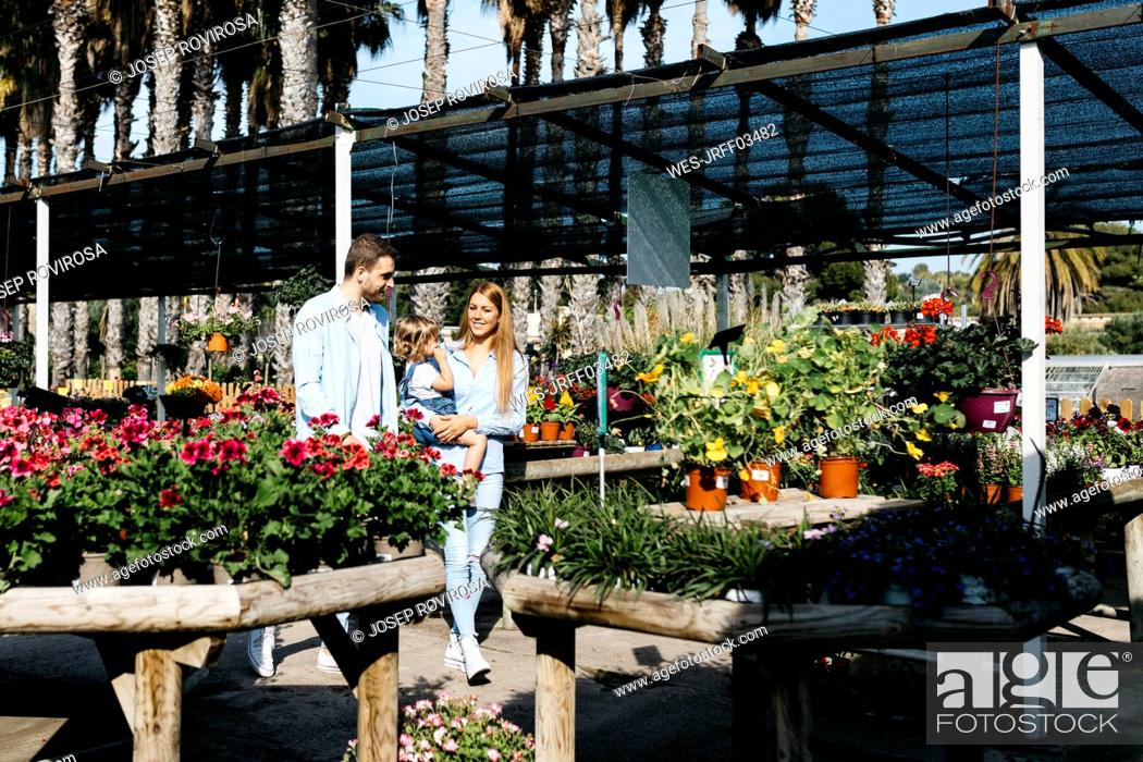 Stock Photo: Mother, father and daughter walking around in a garden center.