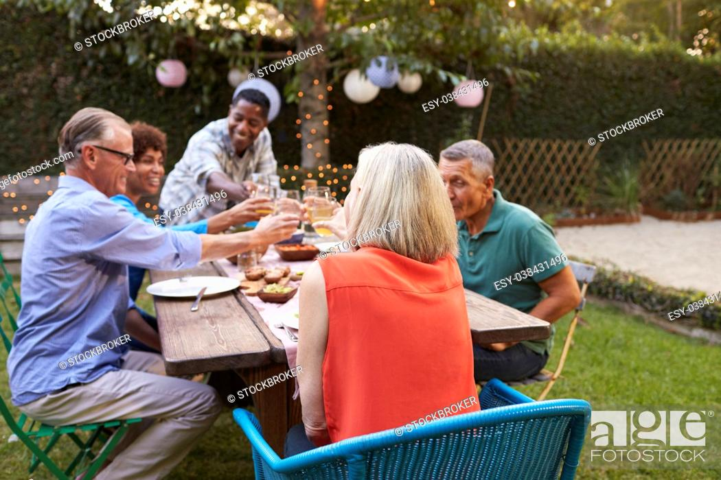 Stock Photo: Group Of Mature Friends Enjoying Outdoor Meal In Backyard.