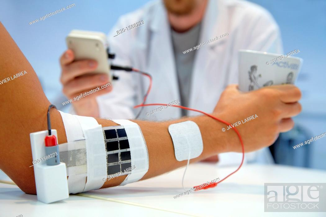 Stock Photo: Researcher placing multipad electrodes in the control arm for the stimulation model for sensor signals  Applications for rehabilitation of lower limb / superior.