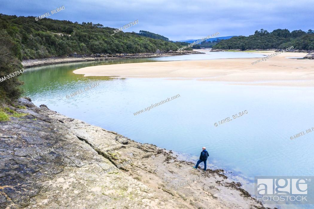 Stock Photo: Man, river and sandy sediments in low tide close to the sea. Isla, Cantabria, Spain, Europe.