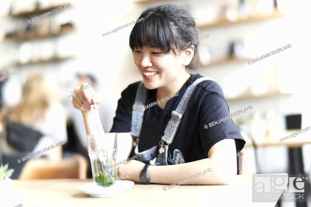 Imagen: Korean woman sitting at table in cafe with drink.
