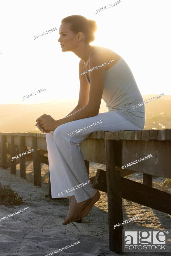 Stock Photo: Woman sitting on a boardwalk and thinking.