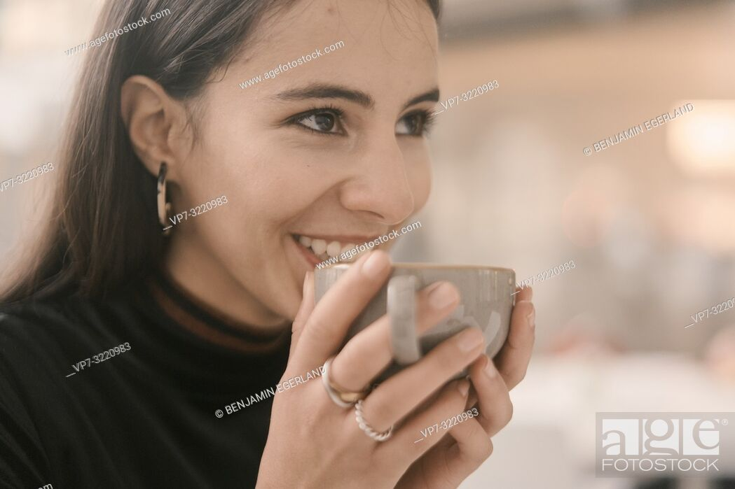 Stock Photo: portrait of happy woman holding coffee cup, in Munich, Germany.