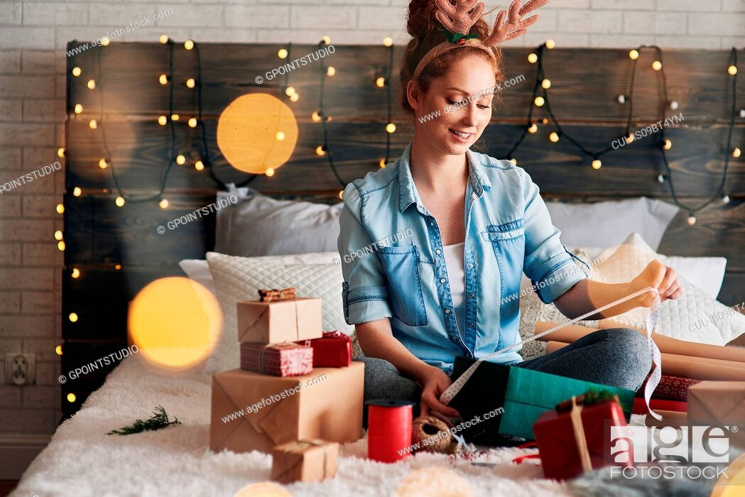 Stock Photo: Woman wrapping Christmas presents on bed.