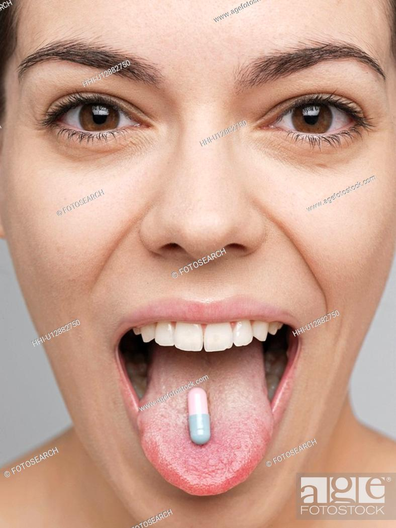 Stock Photo: Vitamin pill on young woman's tongue.